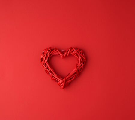 red wicker decorative heart on a red paper background, festive backdrop for Valentine's day