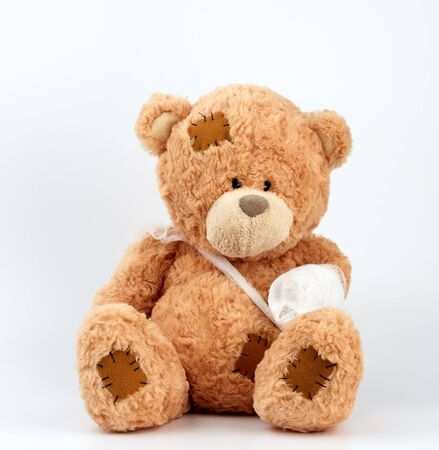 large beige teddy bear with patches sits on a white background, left paw is bandaged with a white medical bandage, concept of pediatrics, treatment of animals