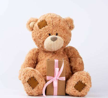 grote beige teddybeer met patches houdt cadeau in doos verpakt in bruin papier, vastgebonden met roze zijden lint op een witte achtergrond, gelukkige verjaardag en Valentijnsdag Stockfoto