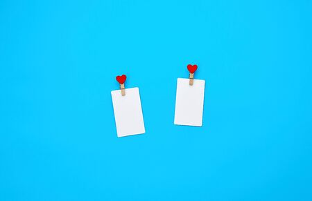 white empty paper rectangular business cards on decorative clothespins with a red heart lie on a blue background, place for an inscription
