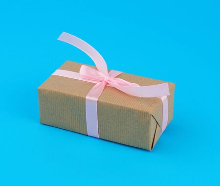 rectangular box wrapped in cinnamon kraft paper and tied up with pink silk ribbon, birthday present and St. Valentine Stock fotó - 138368343