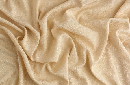 beige satin textile fabric with embroidery elements, piece of canvas for sewing curtains and things, full frame. Crumpled textile satin, great design for any purposes.