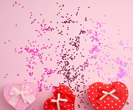 closed red and pink heart-shaped cardboard boxes on a pink background with multi-colored shiny confetti, festive backdrop for birthday, Valentines day