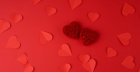 hearts cut out of red paper on a red background, festive backdrop for Valentines Day, flat lay
