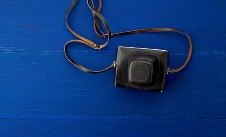 Vintage film camera in a leather case on a wooden blue background, top view Фото со стока