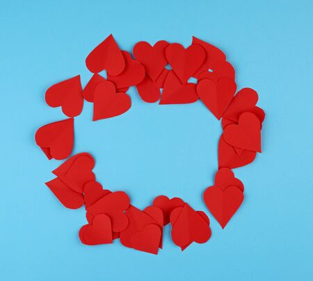 hearts cut out of red paper on a blue background, festive backdrop for Valentines Day, copy space