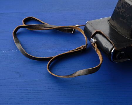 Vintage film camera in a leather case on a wooden blue background, close up