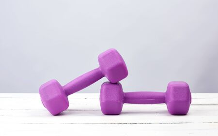 pair of purple plastic dumbbells for sports on a white wooden background, copy space. Fitness training. Healthy lifestyle.
