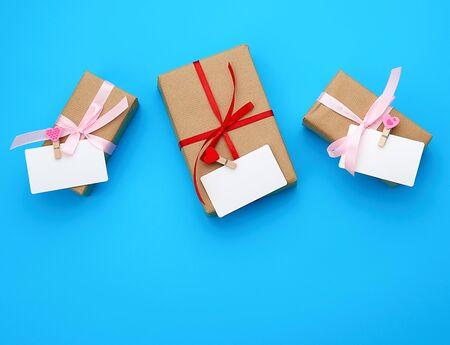 box is wrapped in brown paper and tied with a red thin silk ribbon on a blue background, copy space, holiday is Valentines Day