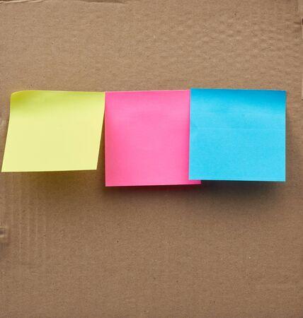 hojas cuadradas en blanco multicolores de pegatinas de papel pegadas sobre una superficie de cartón marrón Foto de archivo