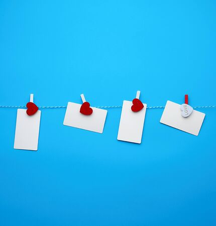 white empty paper rectangular business cards on decorative clothespins with a red heart hanging on a rope, blue background, place for an inscription