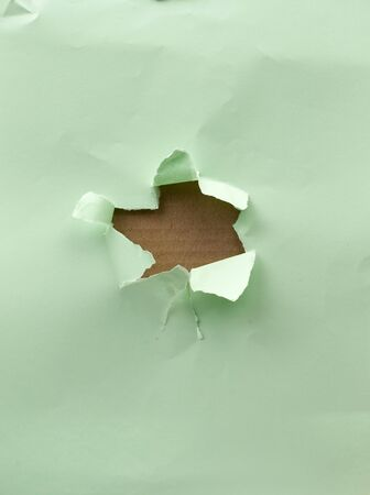 hole in green paper with torn and curved edges. Blank template.