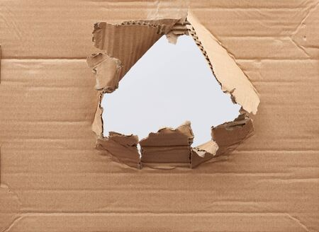 hole in brown cardboard paper with torn and curved edges. Blank template. Stockfoto