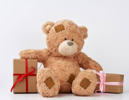 big beige teddy bear with patches, a stack of gifts in boxes wrapped in brown paper, tied with silk ribbon on a white background, happy birthday and valentines day Banco de Imagens