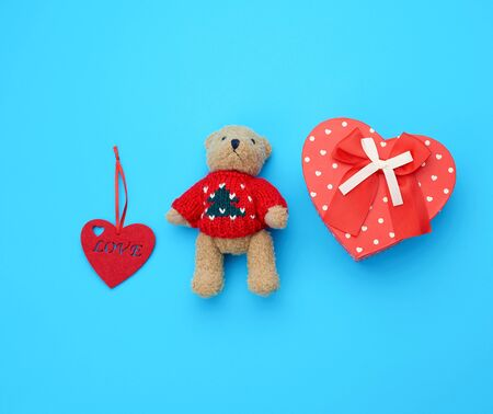 red cardboard box in the form of a heart and little brown teddy bear on a light blue background, top view Foto de archivo - 138468481