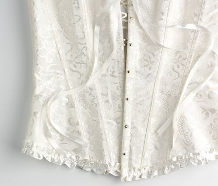 fragment of a white satin corset with lacing, front closure with iron buttons, white background