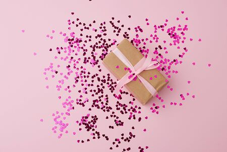 brown gift box wrapped in paper and tied with silk pink ribbon on a pink background with multi-colored shiny confetti, festive backdrop for birthday, valentine's day Foto de archivo - 138468480