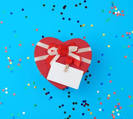 closed red heart-shaped cardboard box on a blue background with multi-colored shiny confetti, festive backdrop for birthday, Valentine's day Foto de archivo - 138468623