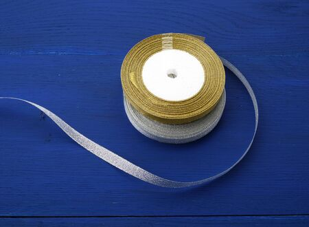 round bobbin with silver and golden ribbon on a blue wooden background, top view