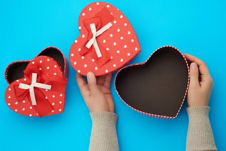 two female hands holding a red cardboard box with a bow on a blue background, concept of giving a gift for a holiday Foto de archivo - 138471978