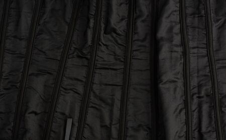 fragment of the inside of a black satin corset with lacing, clothing item