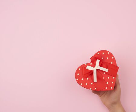 female hand holding a red cardboard box with a bow on a pink background, concept of giving a gift for a holiday Foto de archivo - 138472100