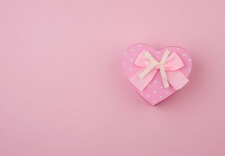 pink gift box in the form of a heart with a bow on a pink background, top view, festive backdrop Foto de archivo - 138471917