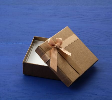 open brown square cardboard empty box, item lies on a blue wooden background, close up