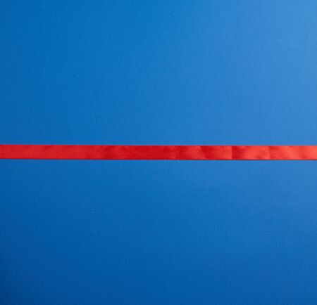 line red silk ribbon lies on a blue background, element for a designer Banco de Imagens