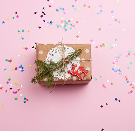 rectangular box wrapped in brown kraft paper and tied with a rope lies on a pink background with scattered confetti, top view