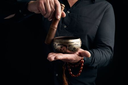 adult man in a black shirt rotates a wooden stick around a copper Tibetan bowl of water. ritual of meditation, prayers and immersion in a trance. Alternative treatment