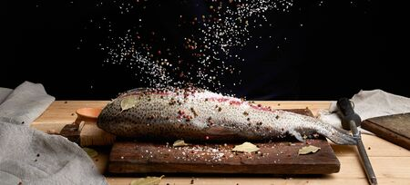 headless salmon fillet on a wooden board sprinkled with large white salt and pepper, process of cooking fish, low key