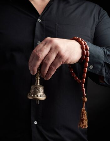adult man in a black shirt holds a copper Tibetan ritual bell, low key. bell represents the feminine principle of excellence in wisdom.