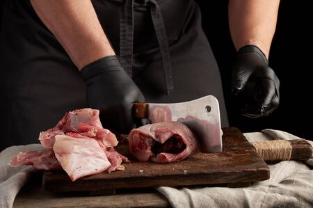 chef in black latex gloves holds a big knife and cuts into pieces raw rabbit meat on a brown wooden cutting board, cooking on a dark background 스톡 콘텐츠