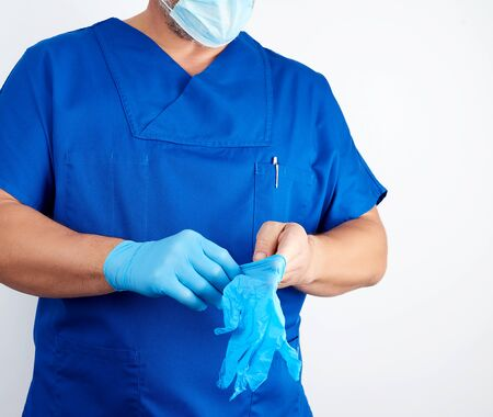 adult male doctor in blue uniform puts on his hands blue sterile latex gloves before surgery, white background Reklamní fotografie