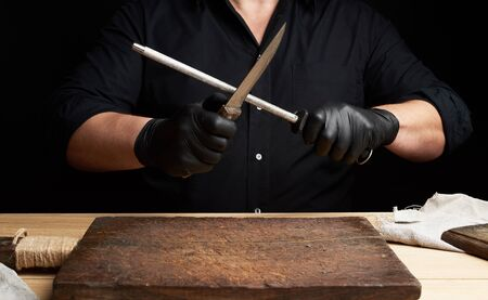 chef in a black shirt and black latex gloves sharpen a kitchen knife on an iron sharpener with a handle above the table, low key Stock Photo