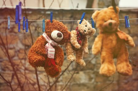 three cute brown wet teddy bears hanging on a clothesline and drying in the fresh air, vintage toning