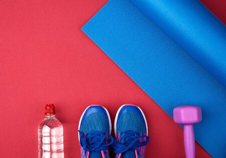 pair of blue training sneakers with laces, bottle of water and a blue twisted neoprene mat on a red texture background, top view, sports set
