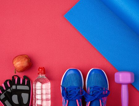 pair of blue training sneakers with laces, bottle of water and a blue twisted neoprene mat on a red texture background, top view, sports set Banque d'images