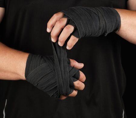 adult athlete stand in black clothes and wrap his hands in black textile elastic bandage before training, black background, muscular body