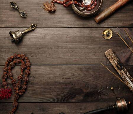 Kupferne Klangschale, Gebetsperlen, Gebetstrommel und andere tibetische religiöse Gegenstände für Meditation und Alternativmedizin auf braunem Holzhintergrund, Kopierraum Standard-Bild
