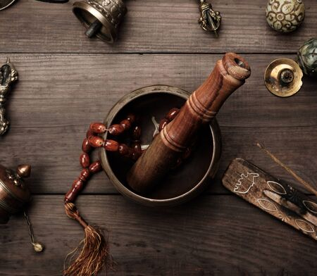 Kupferne Klangschale, Gebetsperlen, Gebetstrommel und andere tibetische religiöse Gegenstände für Meditation und Alternativmedizin auf braunem Holzhintergrund Standard-Bild