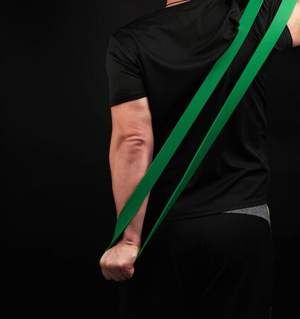 adult athlete in black uniform stands with his back and stretches a green sports elastic band, exercises for the muscles of the arms, dark background