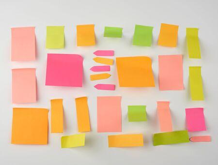 Pegatinas de papel en blanco multicolores de diferentes tamaños y formas sobre un fondo blanco.