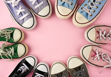 many multi-colored well-worn textile sneakers of different sizes on a pink background, top view, concept, family and team, friendship, copy space