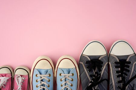 lot of textile worn sneakers of different sizes on a pink background, empty space, family concept