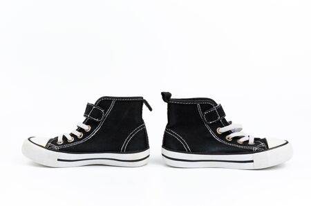black textile sneakers with white tied shoelaces on a white background, pair shoes stand sideways