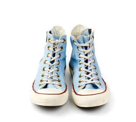 pair of light blue worn textile sneakers with laces and zippers on a white background, front view