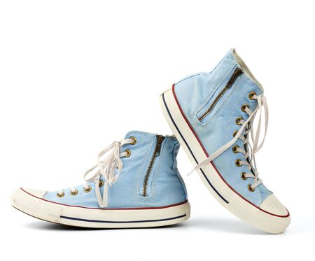 pair of light blue worn textile sneakers with laces and zippers on a white background, side view of shoes