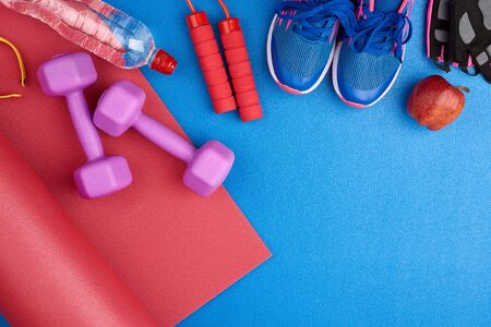 pair of blue training sneakers with laces, bottle of water and a red twisted neoprene mat on a blue texture background, top view, sports set